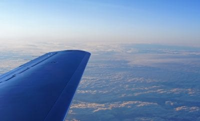above the clouds plane wing in the sky private jet